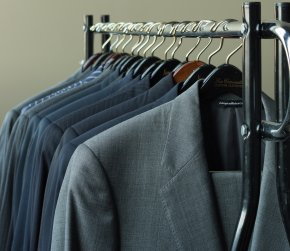 Photograph of business suits hung on a line.